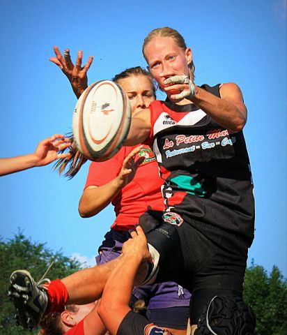 Two women supported in the air at a lineout during a Rugby game. Representing the teams of Ormstown and Montreal in the 2014 1st division Quebec Rugby Finals.