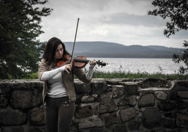 Woman playing a violin in front of an old, short, stone wall.