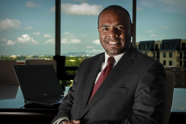 Kevin Persaud in a boardroom with a lovely view in Montreal's West Island.