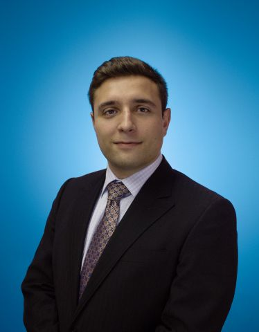 Portrait of Mike Fiacco, accountant at Sinclair, with a blue background.